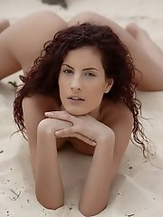 Curly redhead Leanna posing nude on the sand by the rocky beach